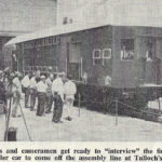 """Reporters and cameramen get ready to """"interview"""" the first double deck trailer car to come of the assemlby limne"""